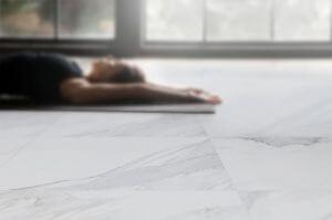 Frau auf Yogamatte am Boden liegend
